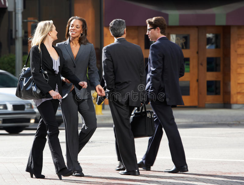 Deux femmes d'affaires causant tout en traversant la rue photos stock