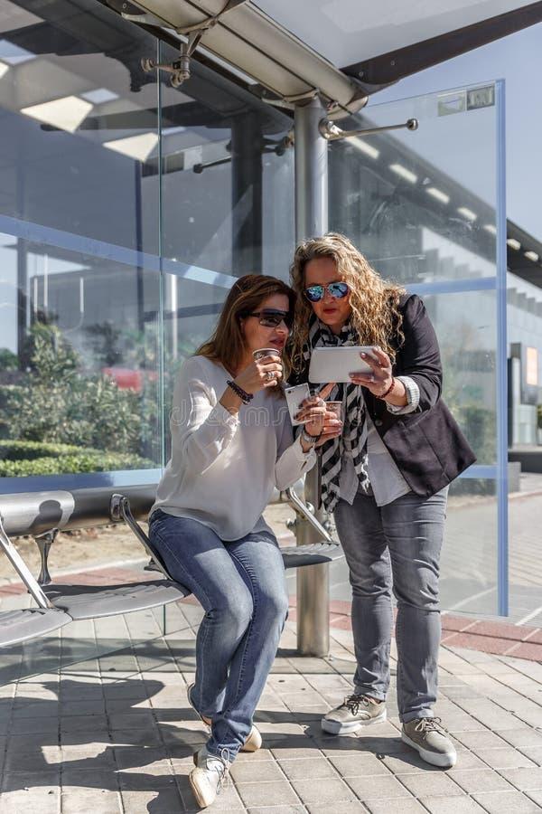 Deux femmes d'affaires causent et prennent un café tout en attendant à un arrêt d'autobus, un beau jour images stock