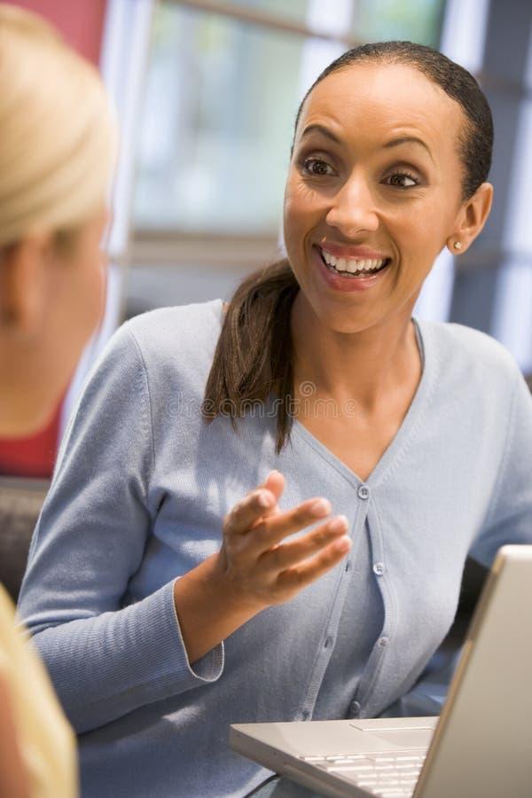 Deux femmes d'affaires dans la salle de réunion avec parler d'ordinateur portatif images libres de droits