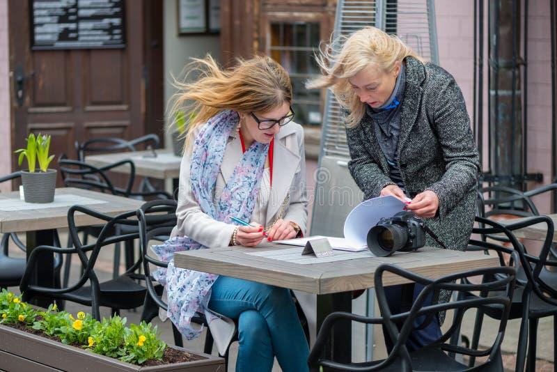 Deux femmes d'affaires dans un café extérieur ont fermé l'affaire et le signe t image libre de droits