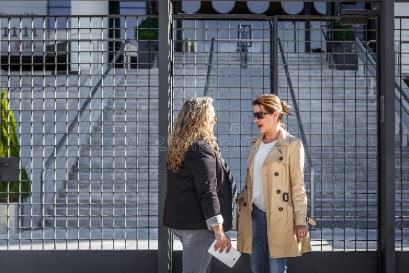 Deux femmes d'affaires discuter quelques choses à l'entrée d'un immeuble de bureaux photo stock