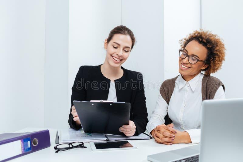 Deux femmes d'affaires gaies avec le presse-papiers fonctionnant ensemble image stock