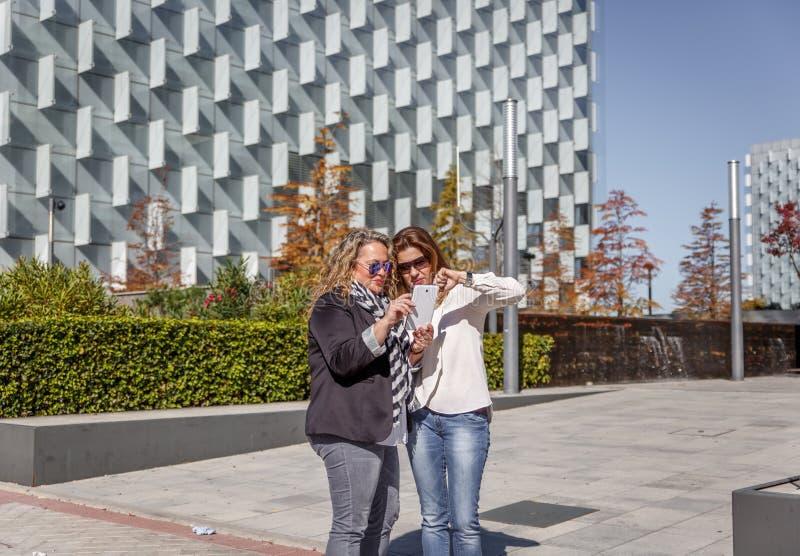 Deux femmes d'affaires mûres dans des vêtements sport causent tout en passant en revue quelque chose sur un comprimé, au milieu d photographie stock libre de droits