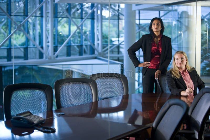 Deux femmes d'affaires sérieuses dans la salle de réunion photographie stock