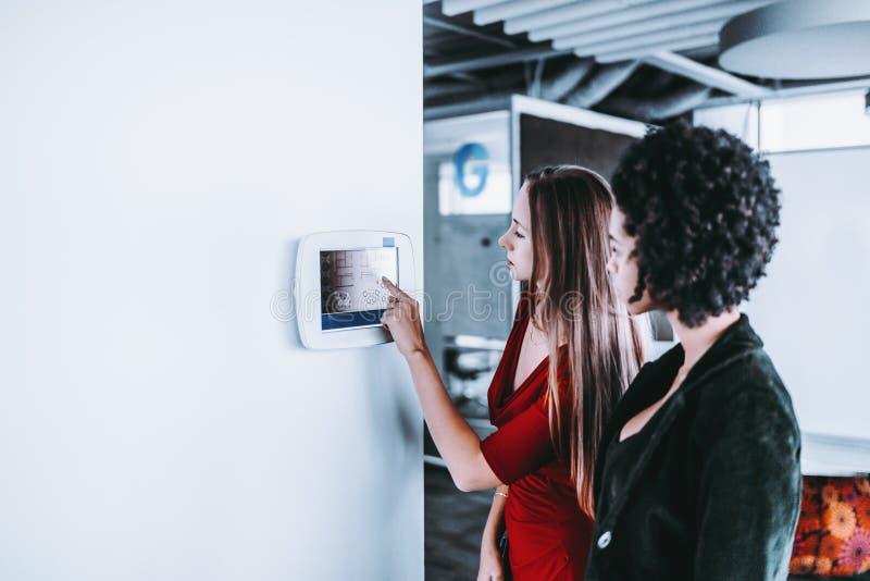 Deux femmes d'affaires s'approchent du terminal de contrôle dans le bureau image stock