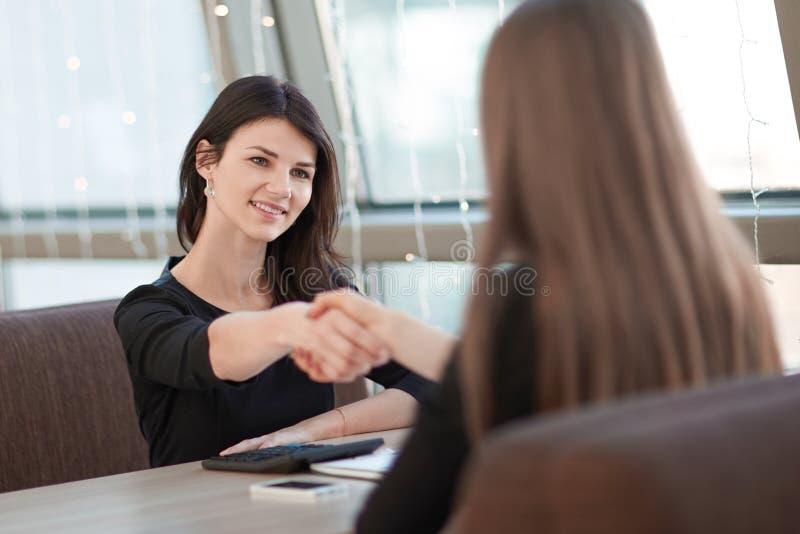 Deux femmes d'affaires se serrant la main lors d'une réunion informelle photo stock
