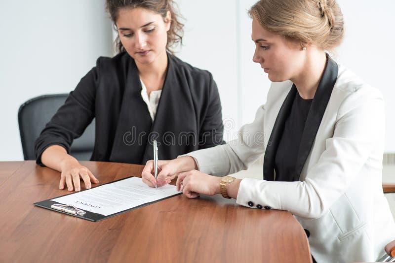 Deux femmes d'affaires signant un document photographie stock libre de droits