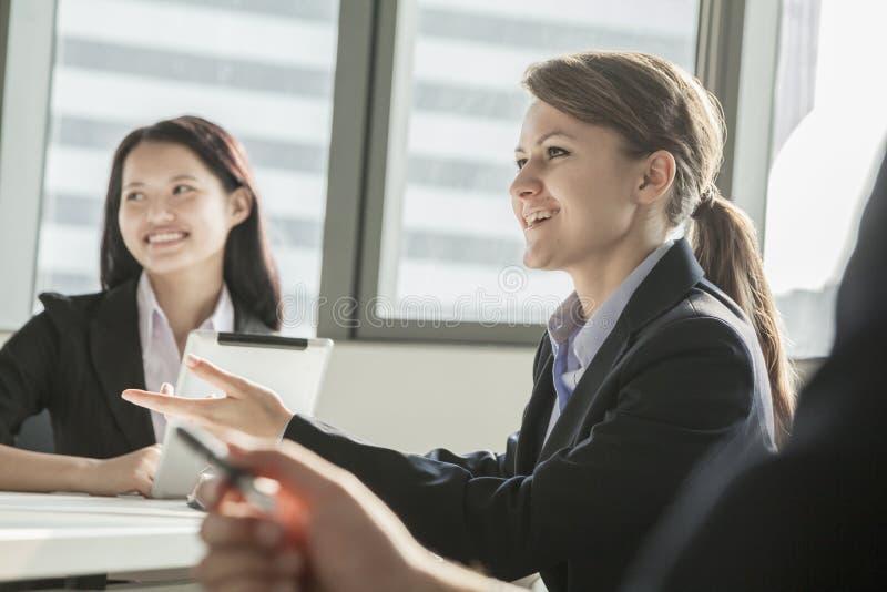 Deux femmes d'affaires souriant, discutant, et faisant des gestes au cours d'une réunion d'affaires images libres de droits