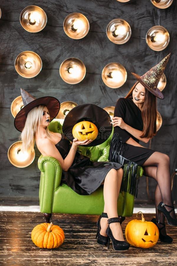 Deux femmes dans des costumes de Halloween sur la partie se reposant sur la chaise au-dessus du fond d'ampoule photos libres de droits