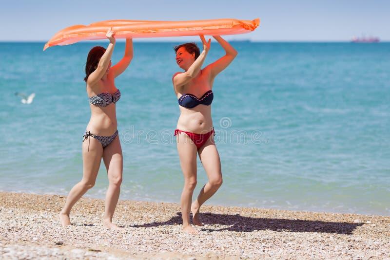 Deux femmes dans des maillots de bain portant le radeau gonflable au-dessus de leurs têtes photographie stock libre de droits