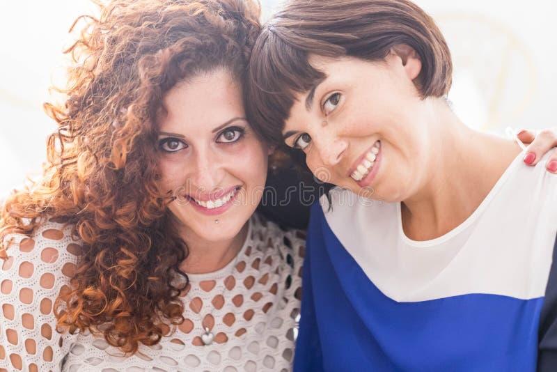 Deux femmes dans l'amitié ou l'étreinte et le séjour de relations ainsi que le grands sourire et amusement joie sur ses visages e photo libre de droits