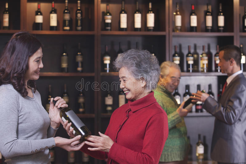 Deux femmes dans le premier plan achetant et discutant le vin, deux hommes à l'arrière-plan photo libre de droits
