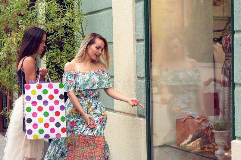 Deux femmes dans les achats regardant la fenêtre de magasin dans la ville image libre de droits