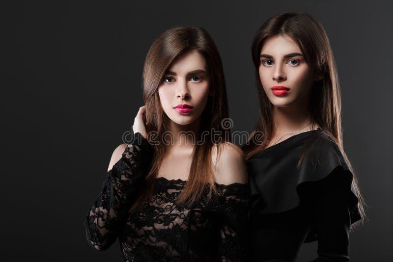 Deux femmes dans une robe noire Jumeaux photos stock