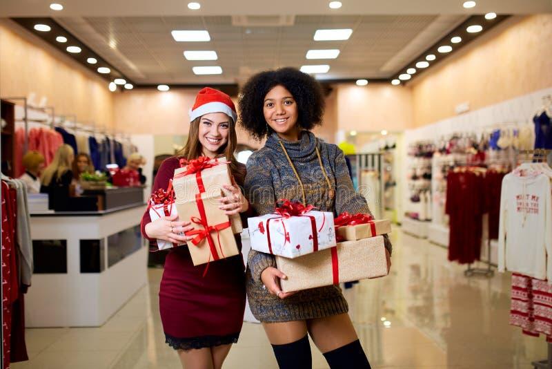 Deux femmes de métis avec des boîte-cadeau dans des mains au magasin Filles ethniques multi souriant avec des présents la nouvell images libres de droits