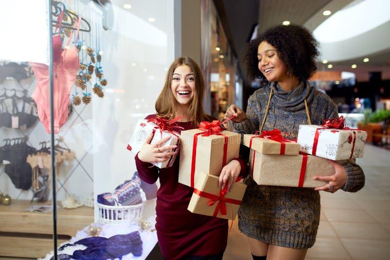 Deux femmes de métis avec des boîte-cadeau dans des mains près de storewindow Filles ethniques multi souriant avec des présents s images libres de droits