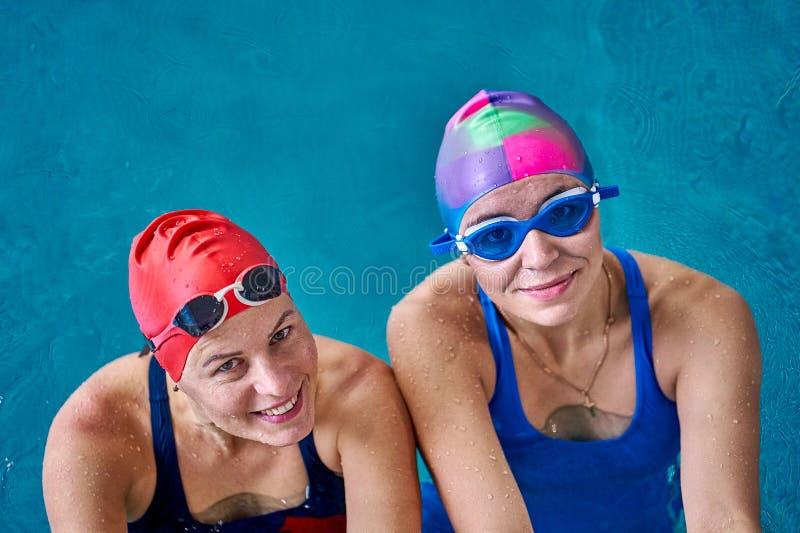 Deux femmes de sourire de nageur détendant dans la piscine après un bain images stock