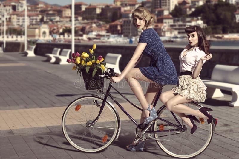 Deux femmes de vintage sur la bicyclette près de la mer photo libre de droits