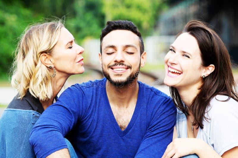 Deux femmes embrassant l'homme bel sur ses joues photos libres de droits