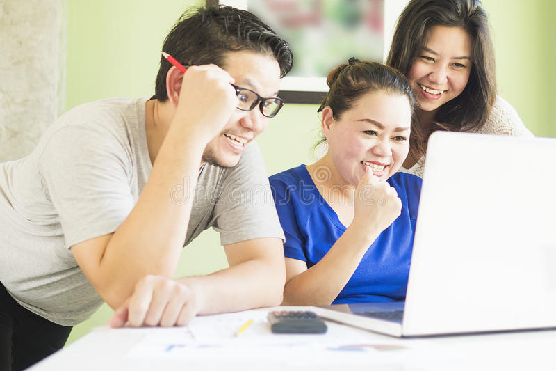 Deux femmes et un homme regardent heureusement l'ordinateur photo libre de droits