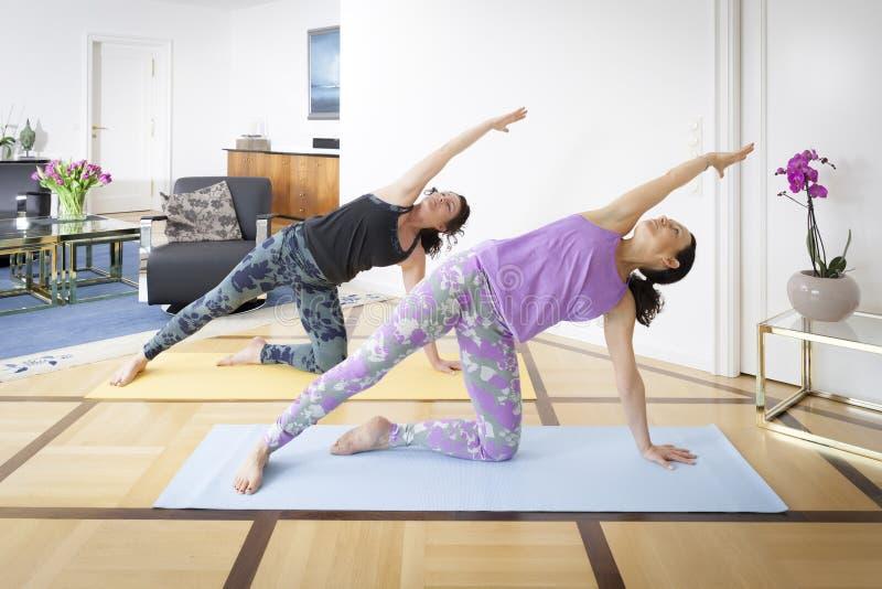 Deux femmes faisant la pose de Vasisthasana de yoga à la maison photos libres de droits