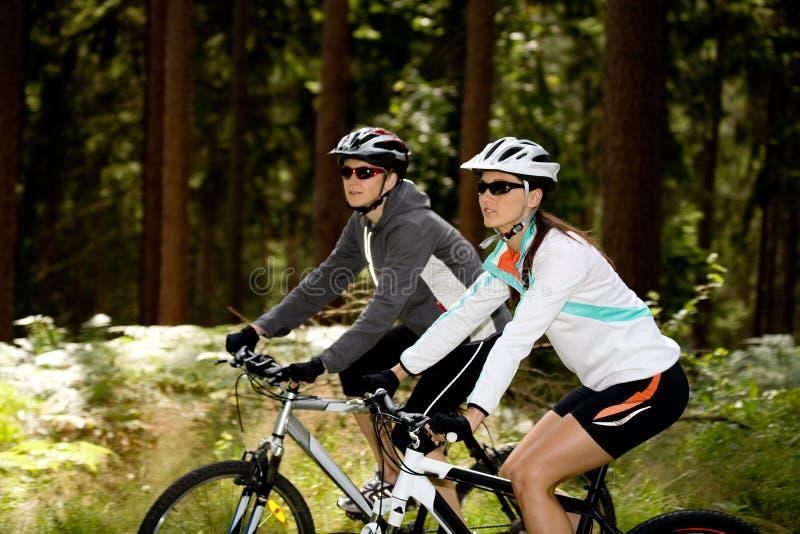 Deux femmes faisant un cycle dans la forêt photographie stock libre de droits