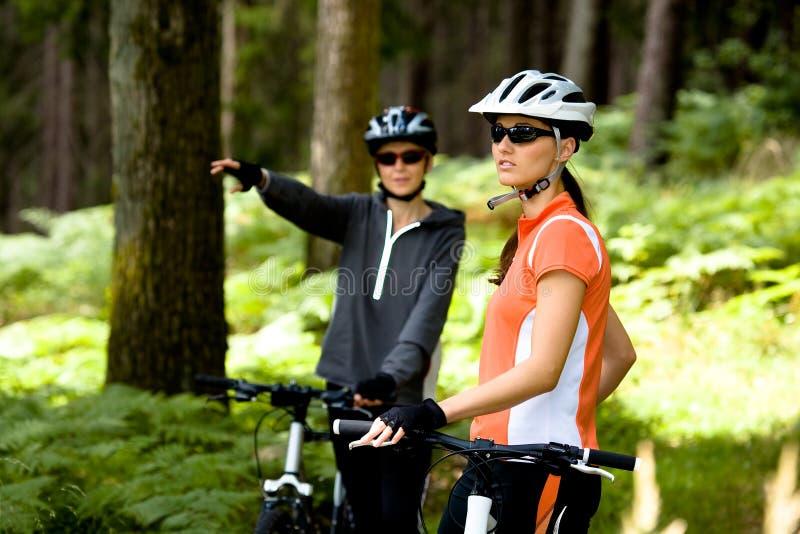 Deux femmes faisant un cycle dans la forêt image libre de droits