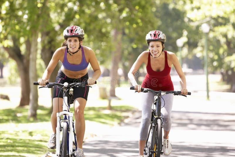 Deux femmes faisant un cycle par le parc images stock
