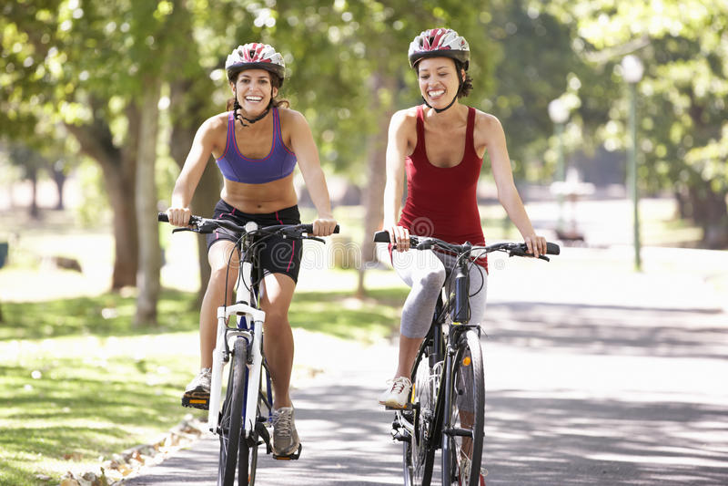 Deux femmes faisant un cycle par le parc photographie stock libre de droits