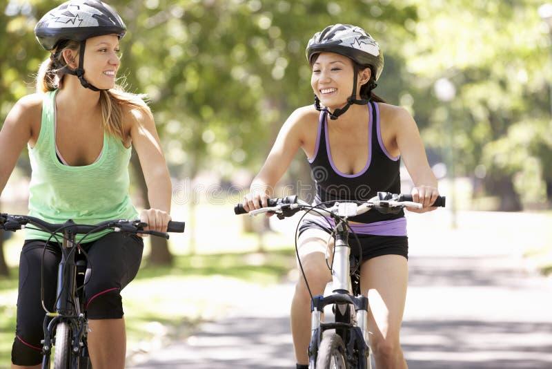 Deux femmes faisant un cycle par le parc photos stock