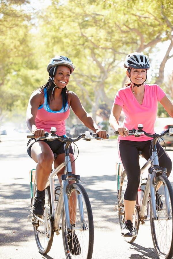 Deux femmes faisant un cycle sur la rue suburbaine photographie stock libre de droits