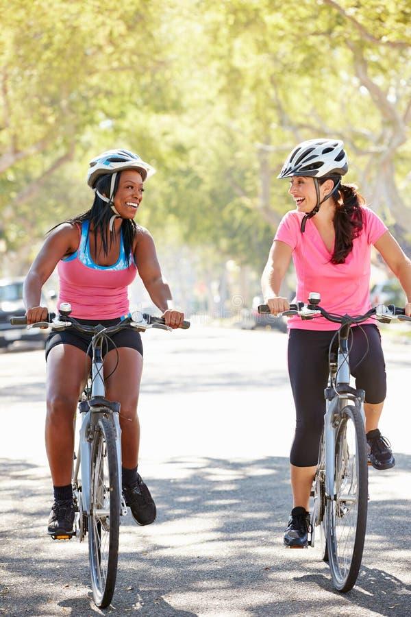 Deux femmes faisant un cycle sur la rue suburbaine images libres de droits