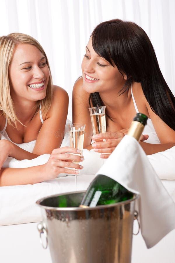 Deux femmes grillant avec le champagne dans la chambre à coucher images libres de droits