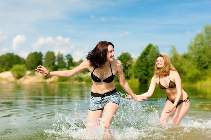Deux femmes heureuses ayant l'amusement au lac en été photographie stock libre de droits