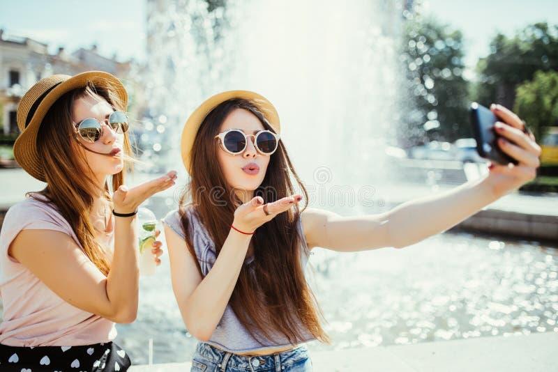 Deux femmes heureuses dans les lunettes de soleil et des chapeaux d'été ont le temps gentil ensemble dans la ville prenant le sel photos libres de droits