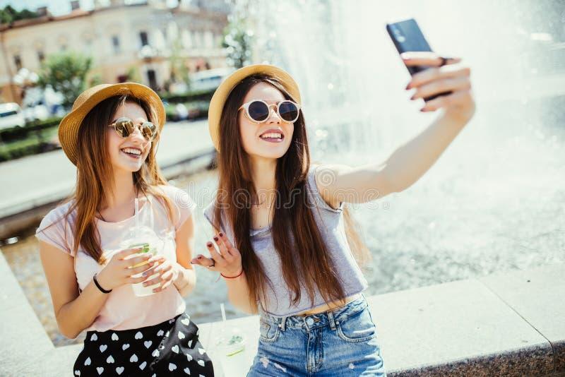 Deux femmes heureuses dans les lunettes de soleil et des chapeaux d'été ont le temps gentil ensemble dans la ville prenant le sel images stock