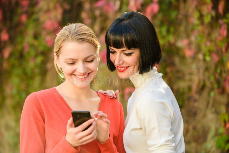 Deux femmes heureuses regardent dans le téléphone Technologie neuve achetez en ligne sur le cyber lundi Achats en ligne de Black  photos stock