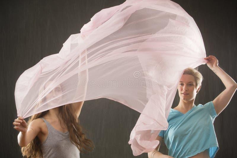 Deux femmes jetant le tissu en l'air rose dans le studio photographie stock