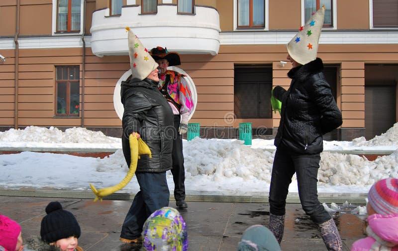 Deux femmes luttent sur l'étape pour l'amusement, enfants observent l'exposition photo libre de droits