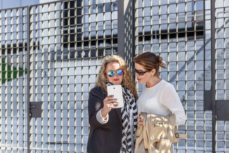 Deux femmes mûres souriant comme elles causent et vérifient un comprimé à la porte de quelques bureaux photographie stock