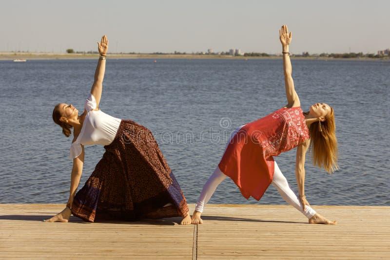 Deux femmes m?res maintenant l'ajustement en faisant le yoga pendant l'?t? photographie stock libre de droits