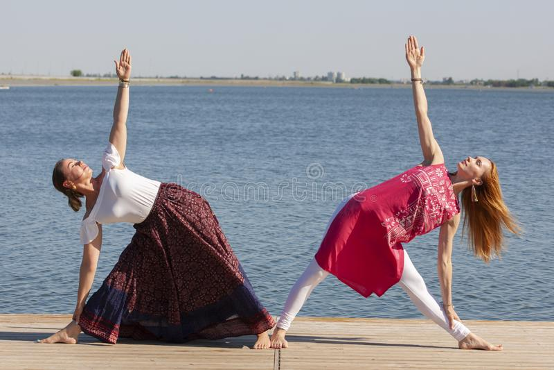 Deux femmes m?res maintenant l'ajustement en faisant le yoga pendant l'?t? images libres de droits