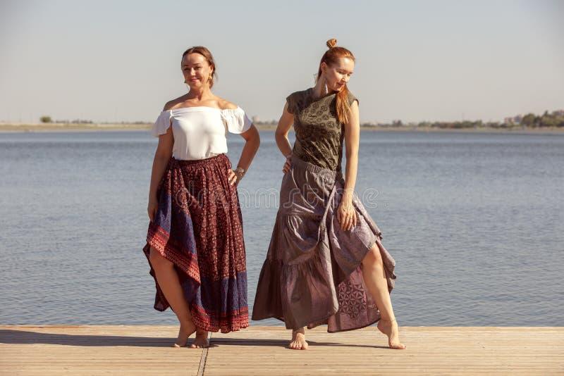 Deux femmes m?res maintenant l'ajustement en faisant le yoga pendant l'?t? images stock