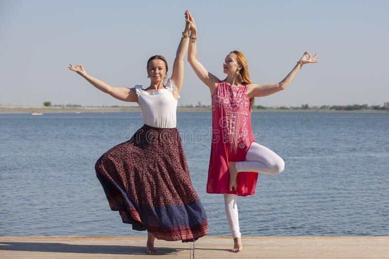 Deux femmes m?res maintenant l'ajustement en faisant le yoga pendant l'?t? image libre de droits