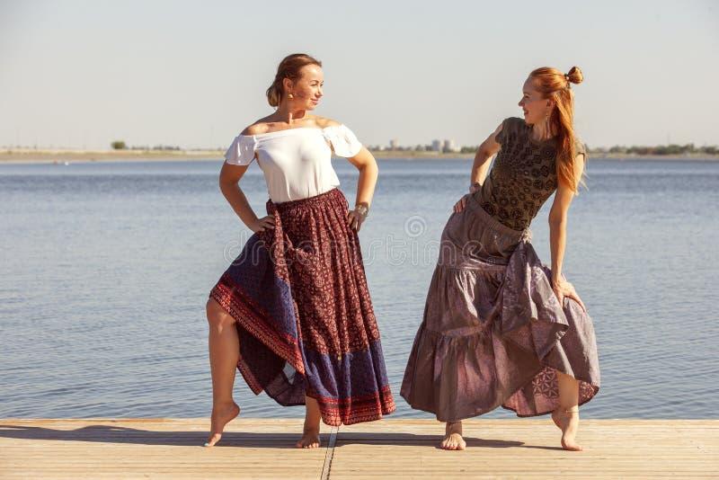 Deux femmes m?res maintenant l'ajustement en faisant le yoga pendant l'?t? image stock