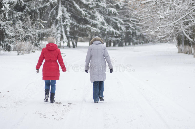 Deux femmes marchant sur une rue vide et neigeuse dans Dniepr, Ukraine chez décembre, 03 2016 images libres de droits