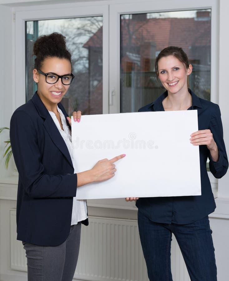 Deux femmes montrent un tableau blanc photos stock