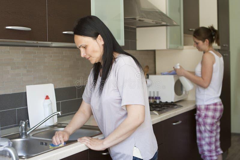 Deux femmes nettoyant les meubles photo stock