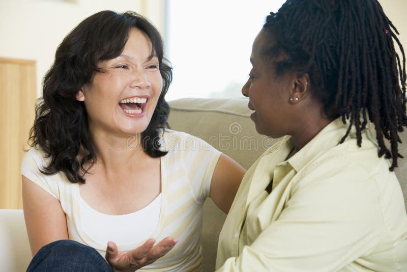 Deux femmes parlant dans la salle de séjour et le sourire photo stock