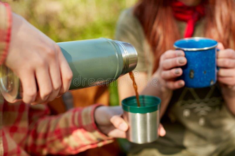 Deux femmes partageant un flacon thermique de café images stock
